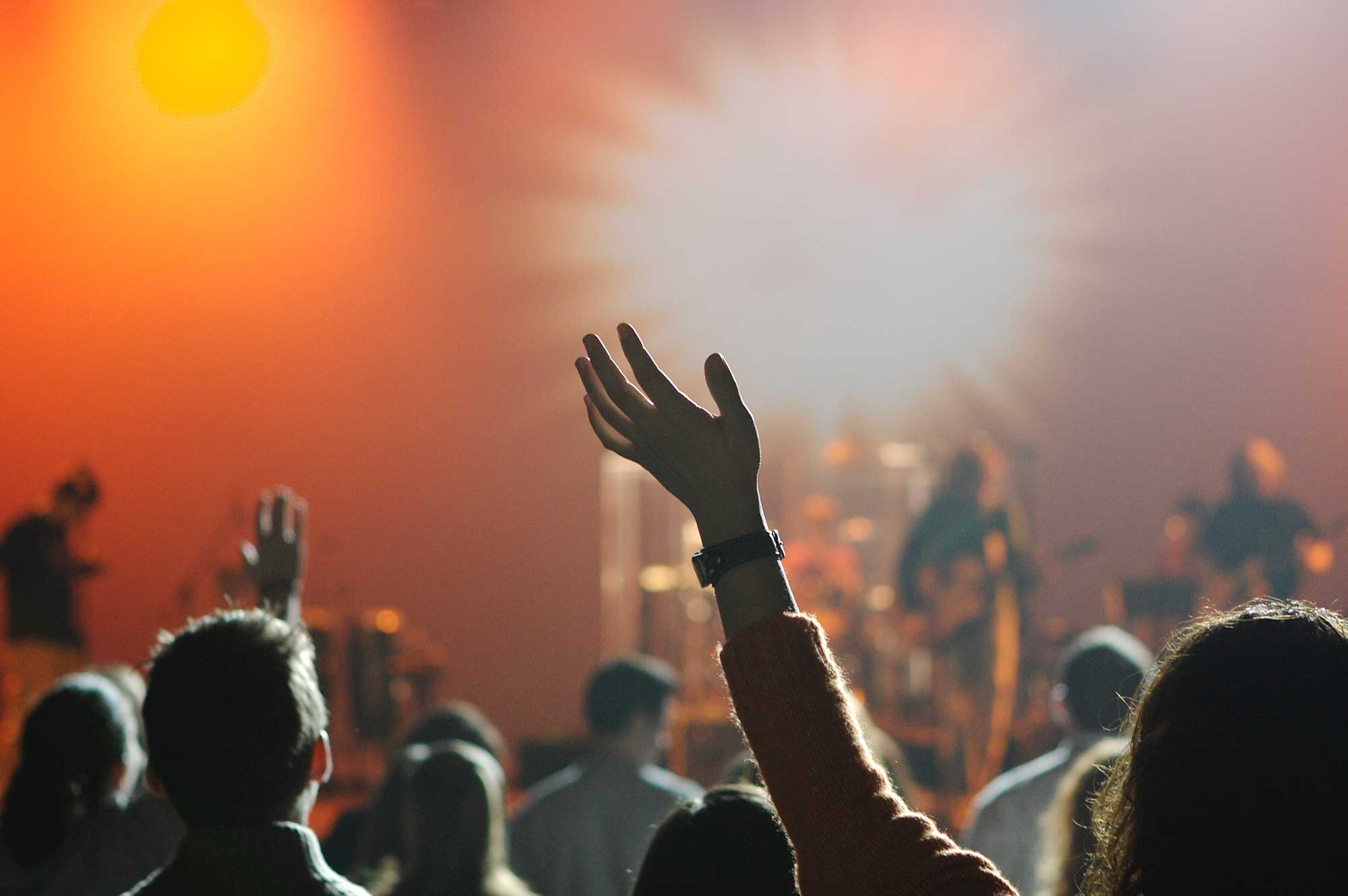 A photo of people with hands raised at a concert